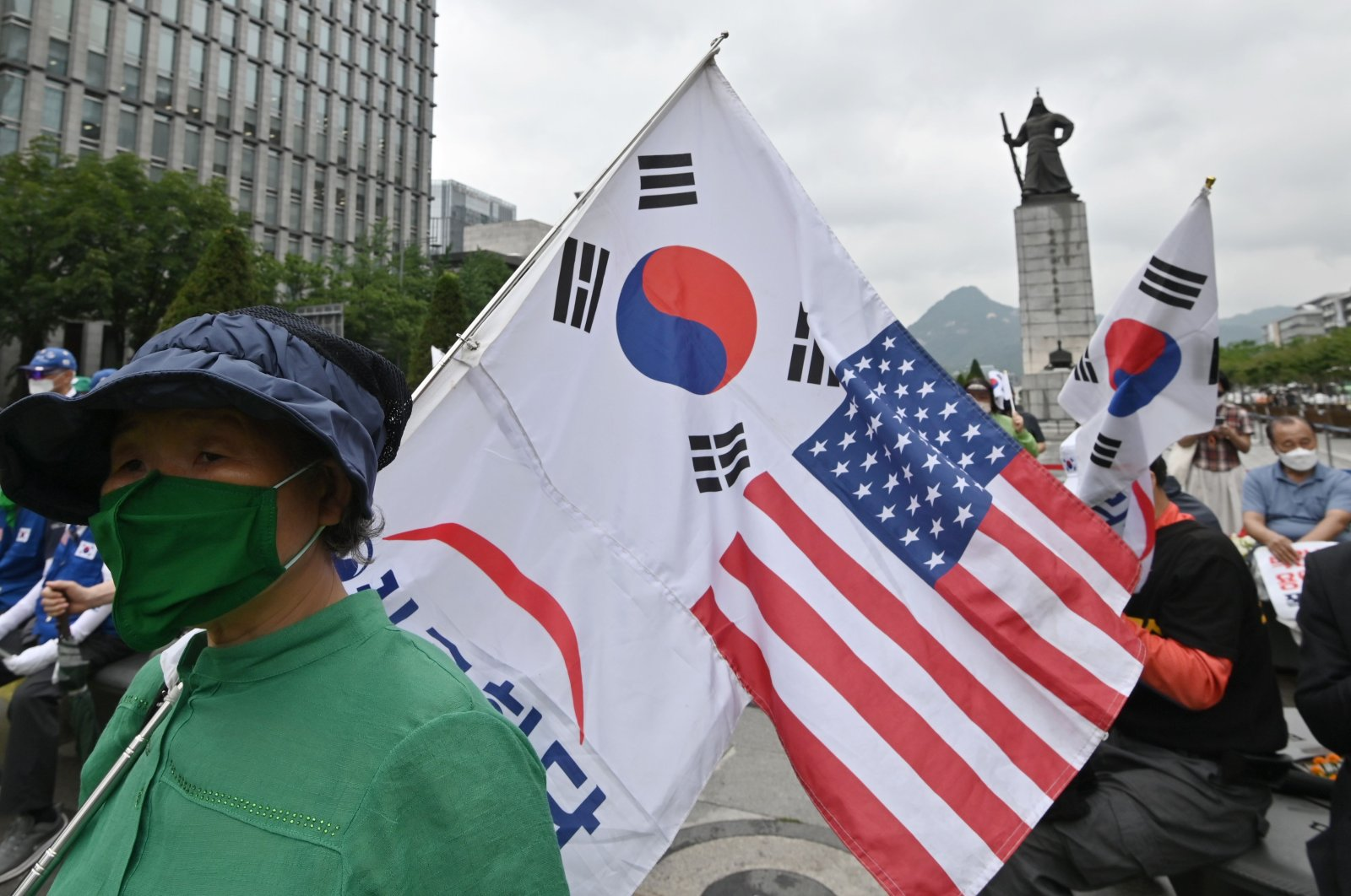 A South Korean woman holds flags of South Korea and the U.S. during a rally commemorating the 70th anniversary of the beginning of the Korean War in Seoul on June 25, 2020. (AFP Photo)