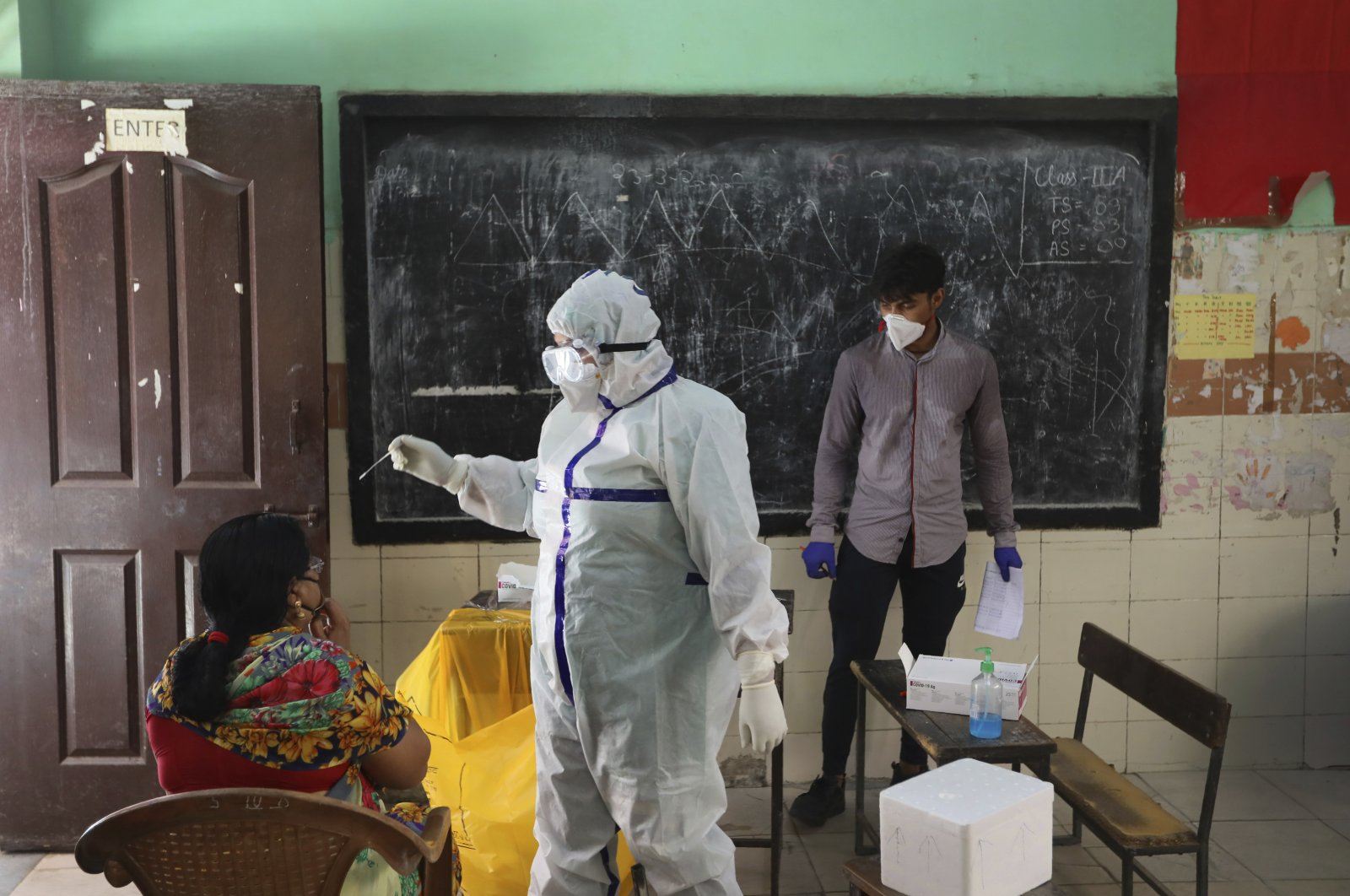 A health worker takes a swab sample of a woman for a COVID-19 test in New Delhi, India, June 24, 2020. (AP Photo)