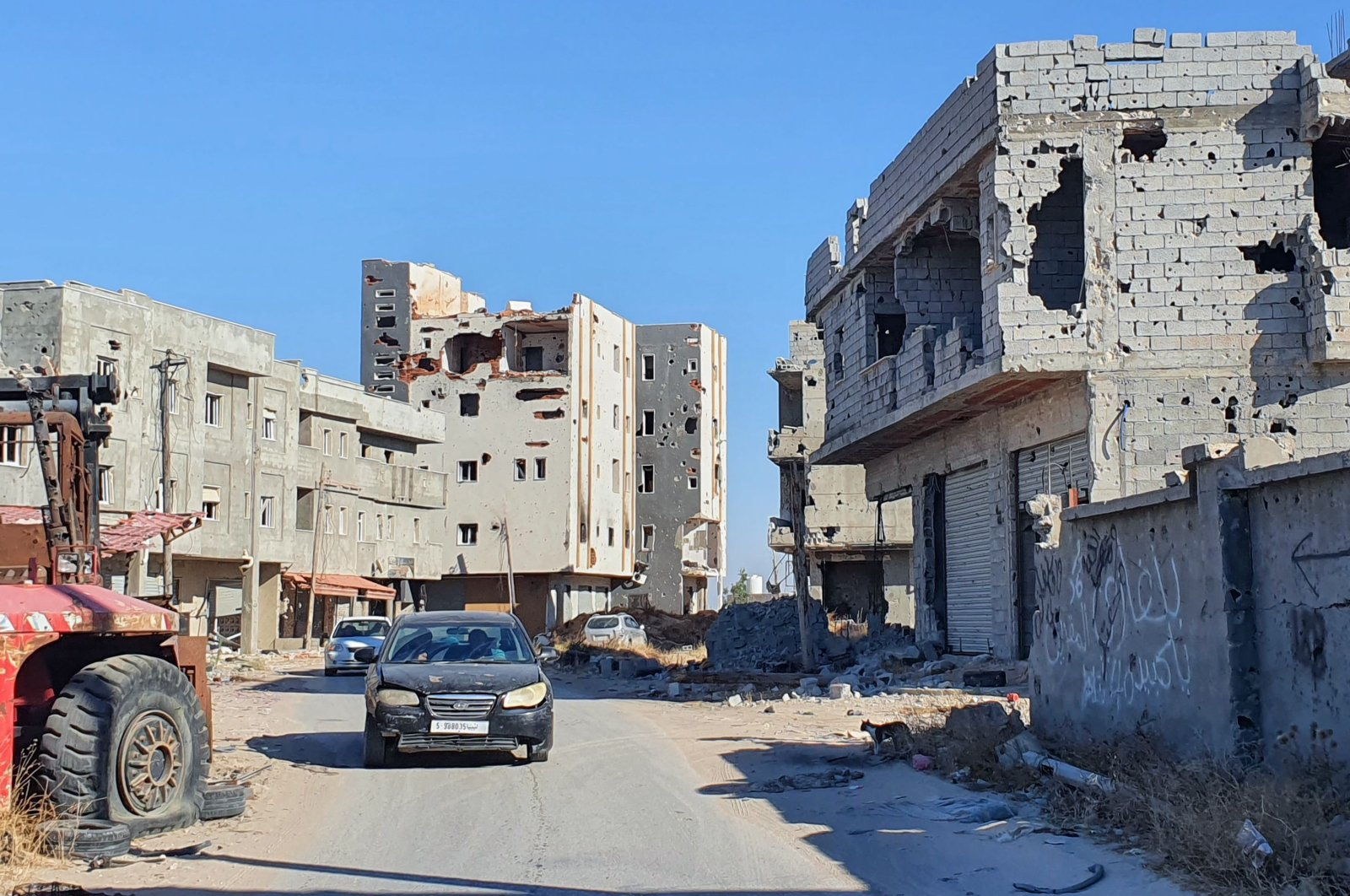 Cars advance on an empty road lined with damaged buildings in the Salaheddin district south of the Libyan capital Tripoli, on June 21, 2020. (AFP Photo)