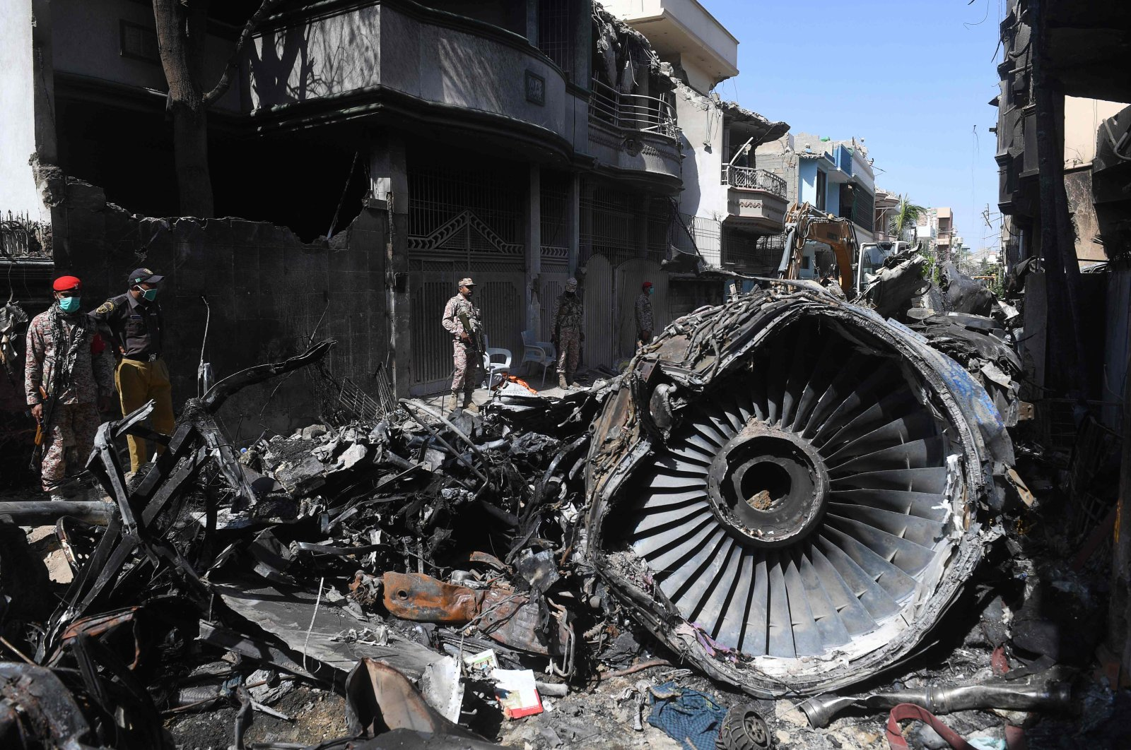 Security personnel stand beside the wreckage of a Pakistan International Airlines aircraft, in Karachi, Pakistan, May 24, 2020. (AFP Photo)