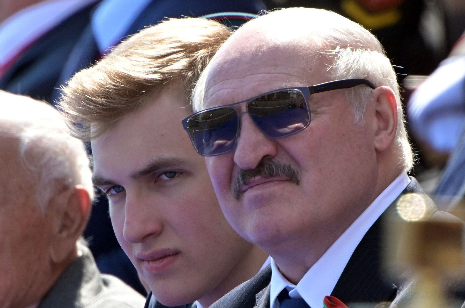 Belarus's President Alexander Lukashenko and his son Nikolai watch a military parade, which marks the 75th anniversary of the Soviet victory over Nazi Germany in World War II, at Red Square in Moscow, June 24, 2020. (Host photo agency via AFP Photo)