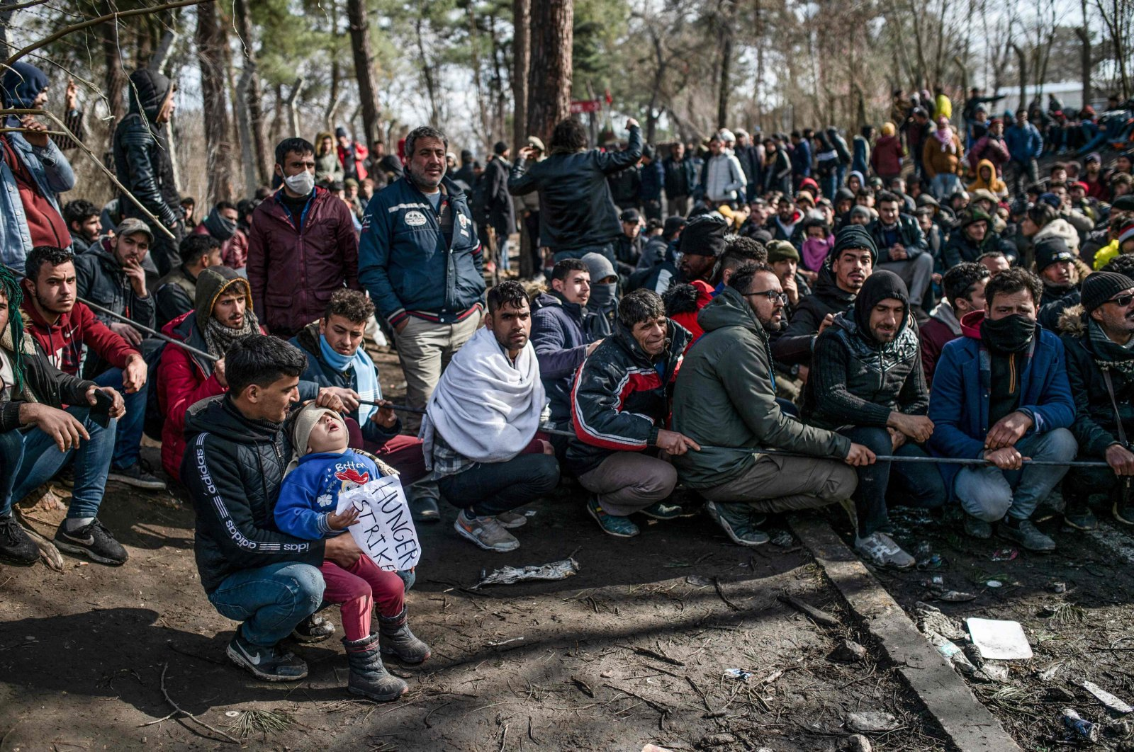 Refugees and migrants wait with their children in the buffer zone at the Turkey-Greece border near the Pazarkule crossing gate in Edirne, March 5, 2020. (AFP Photo)