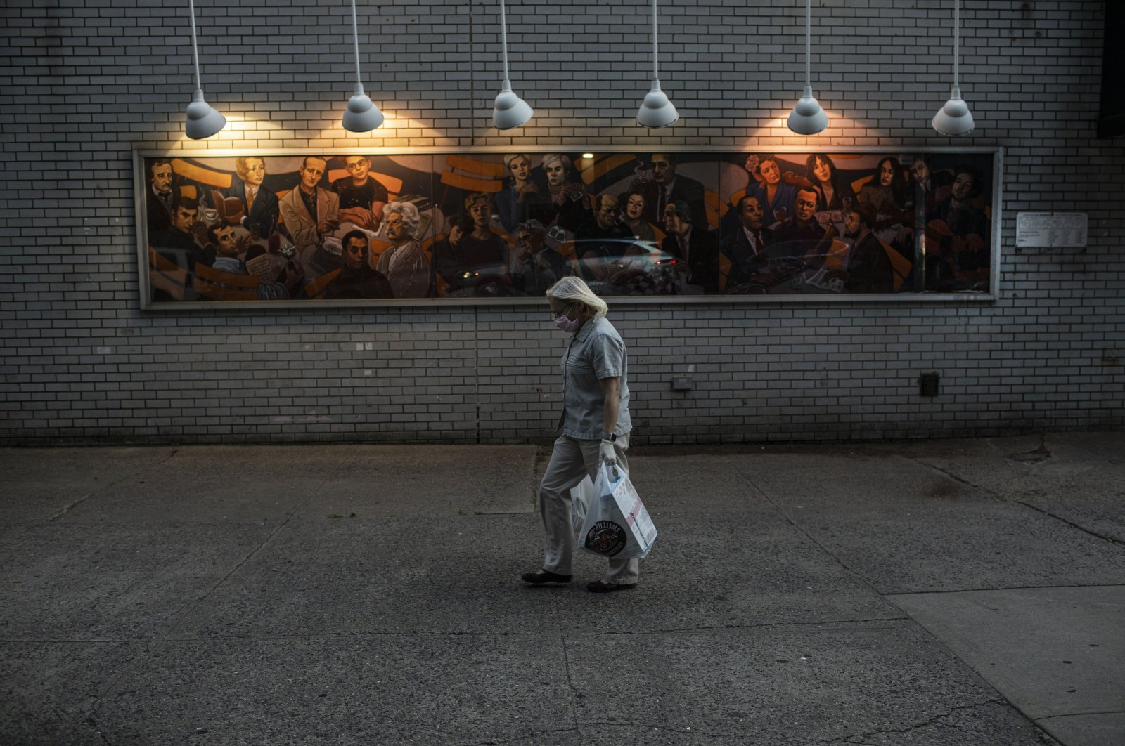 A woman carries shopping bags as she leaves a grocery store, New York City, New York, U.S, June 10, 2020. (AP Photo)