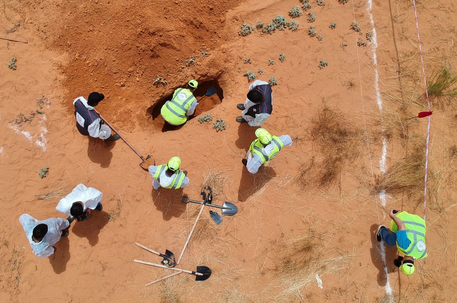 An aerial view shows Libyan experts searching for human remains during the exhumation of mass graves in Tarhuna, a city recently retaken from forces loyal to putschist Gen. Khalifa Haftar, southeast of the capital Tripoli, Libya, June 23, 2020. (AFP Photo)