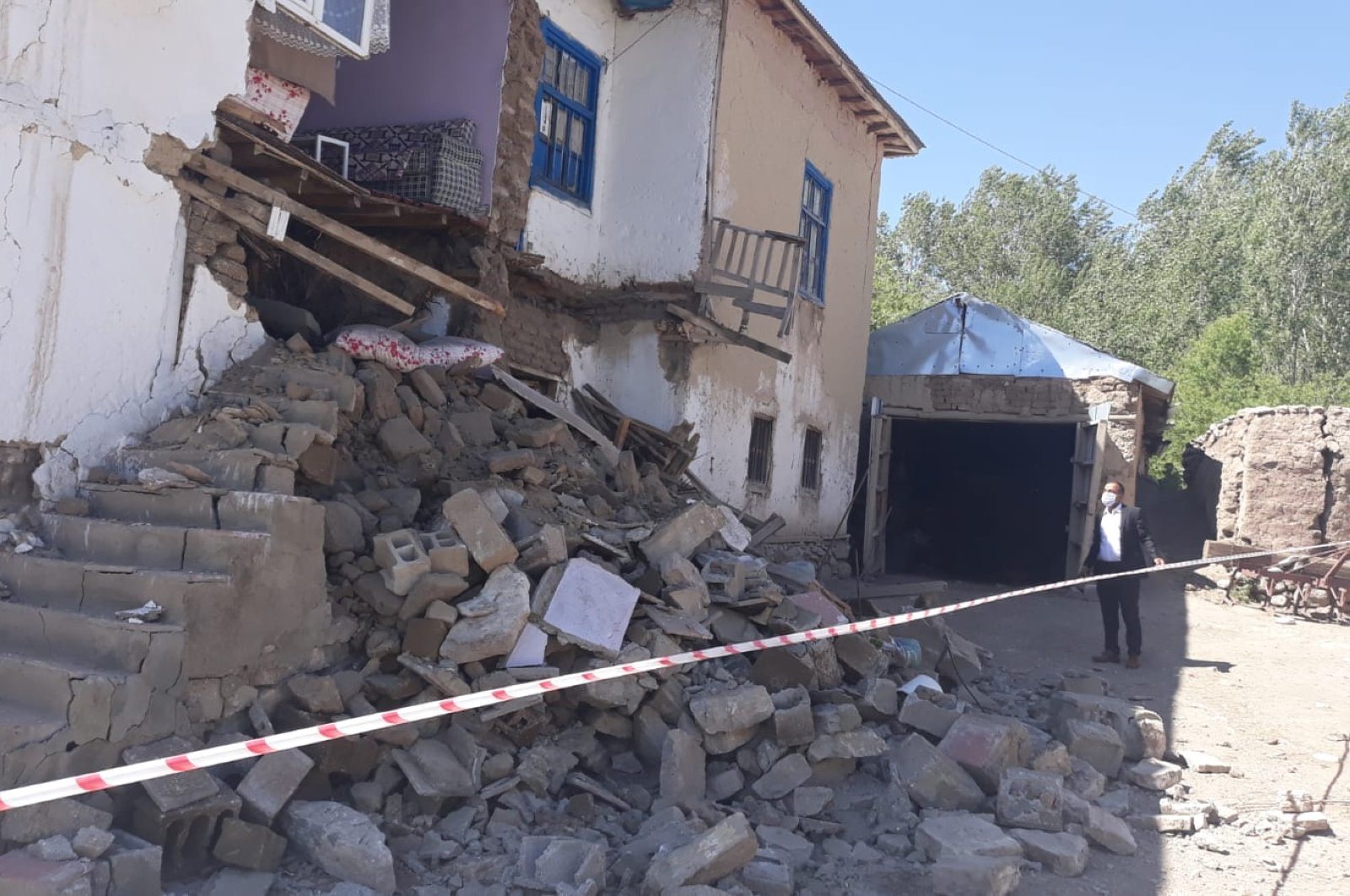 A man stands outside a partially collapsed building in the Gürpınar district, in Van, Turkey, June 25, 2020. (AA Photo)