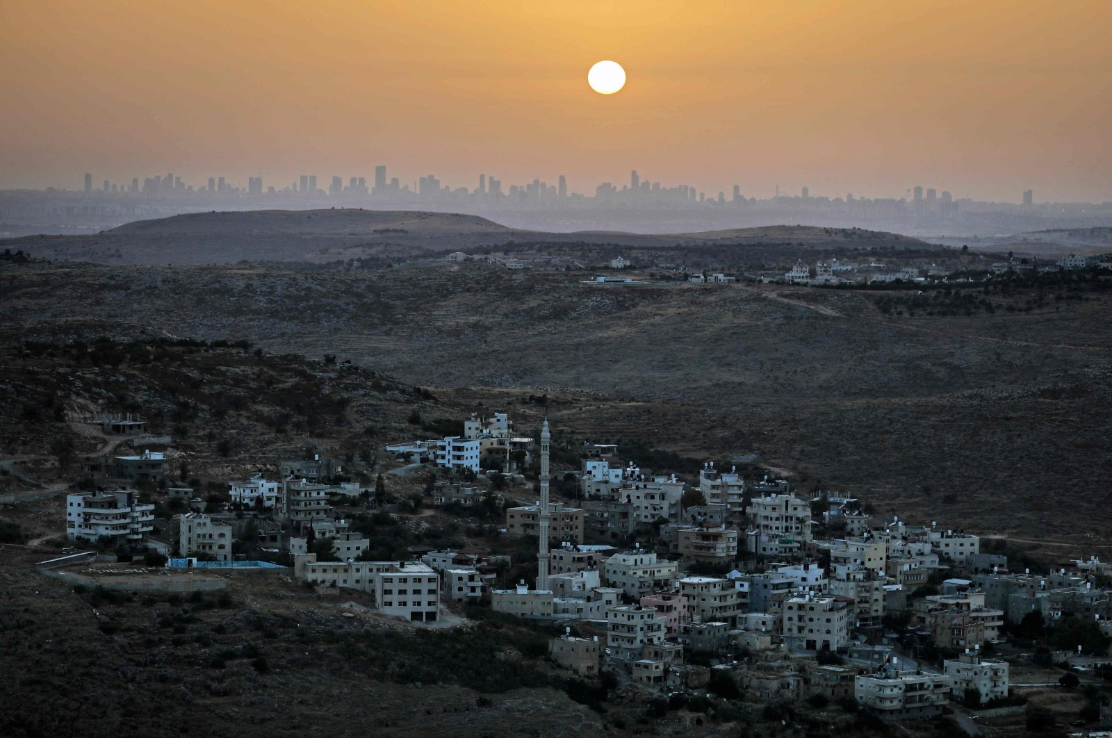 A picture taken from the Israeli settlement of Naale in the occupied West Bank northwest of the Palestinian city of Ramallah shows the skyline of the Israeli coastal city of Tel Aviv, June 17, 2020. (AFP Photo)
