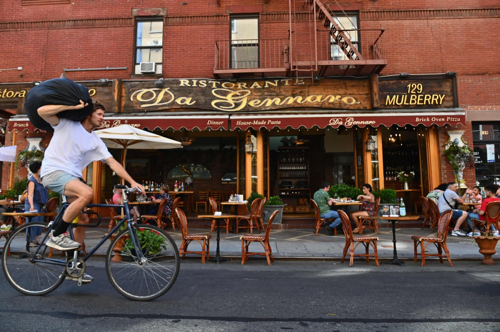 A biker goes past a restaurant with outdoor seating in the Little Italy neighborhood, New York City, June 24, 2020. (AFP Photo)