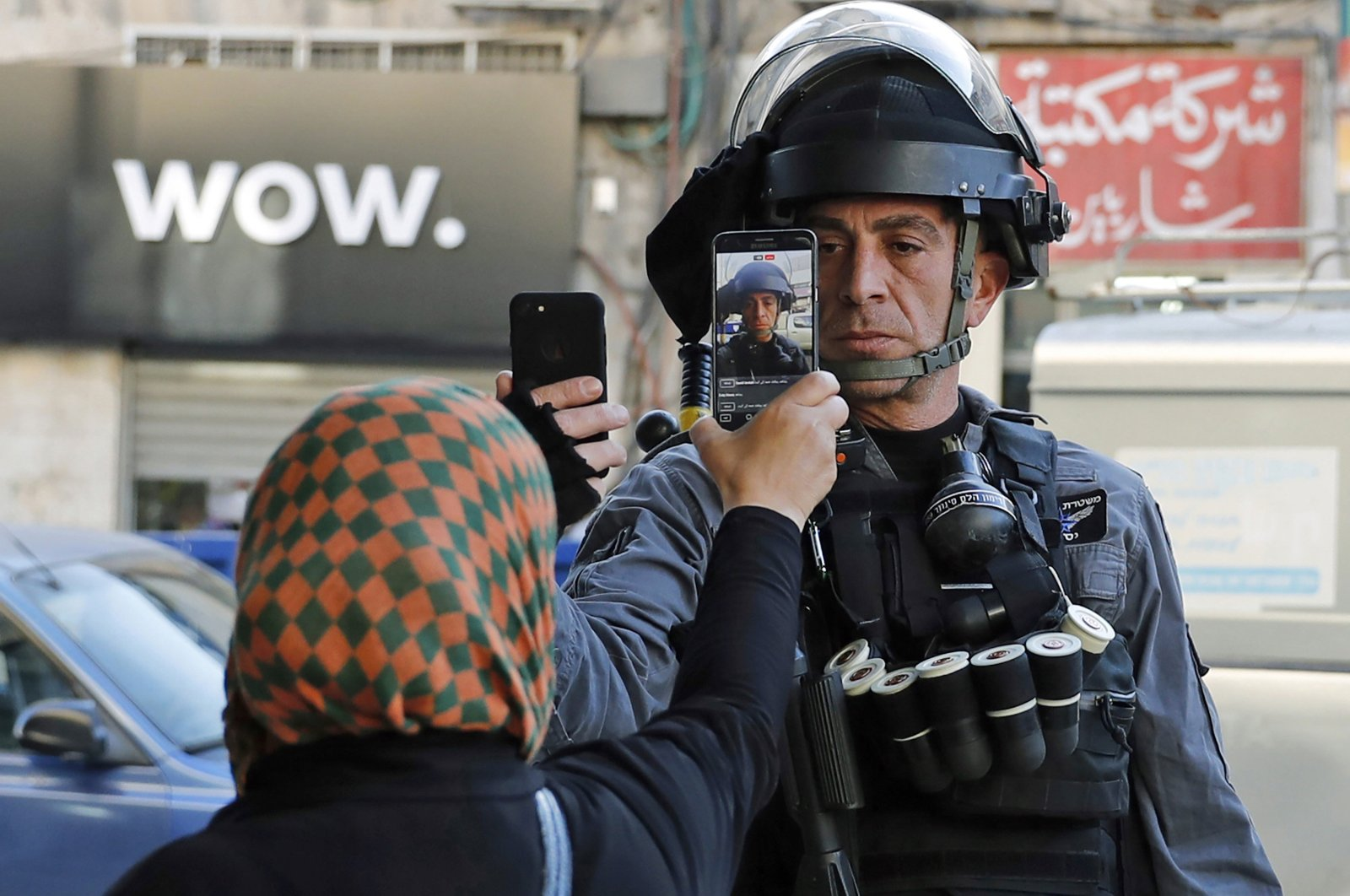 A Palestinian woman takes a picture of a member of the Israeli security forces as he takes her picture in a street in Jerusalem, Dec.16, 2017.