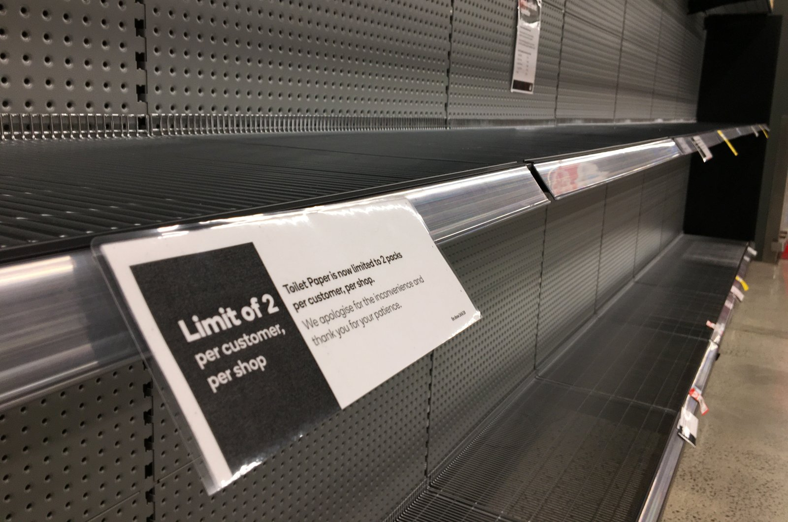 Signage for product limits on an empty toilet paper shelf in a Woolworths Supermarket in Melbourne, June 26, 2020. (Reuters Photo)