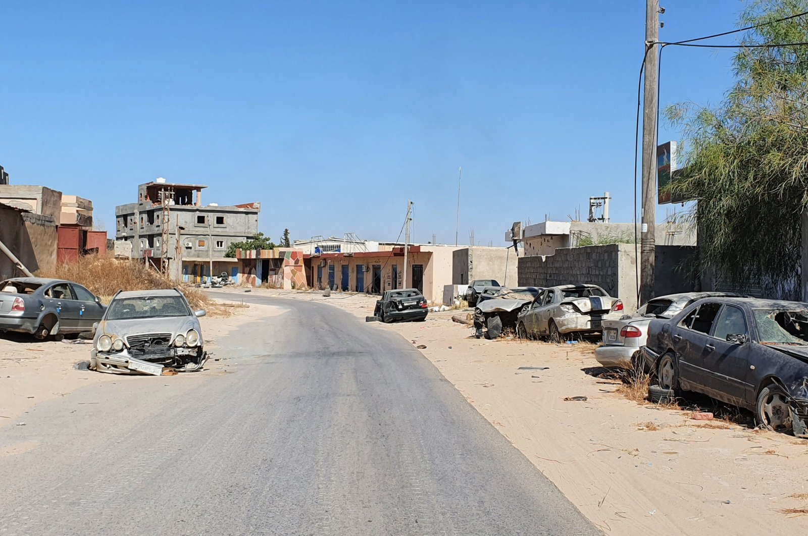 Damaged cars line a road in the Salaheddin district south of the Libyan capital Tripoli, June 21, 2020. (AFP Photo)