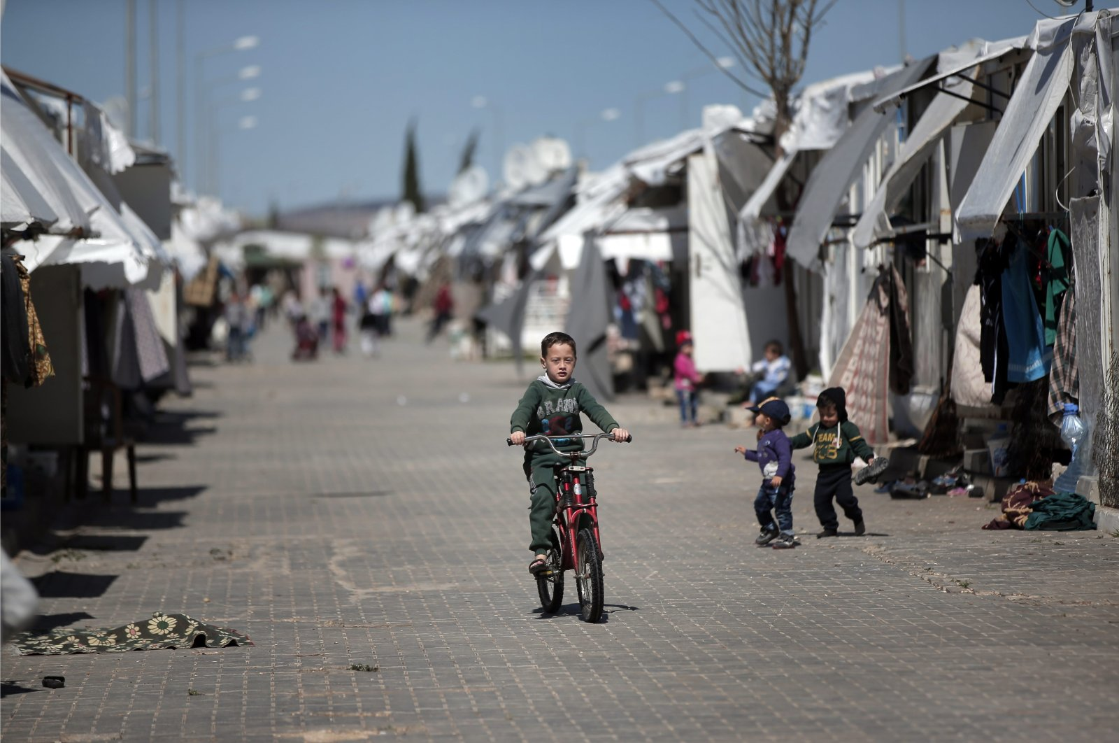 A Syrian refugee child rides his bike at the Öncüpınar Camp for refugees next to the border crossing with Syria in Turkey's Kilis province, March 17, 2016. (AP File Photo)