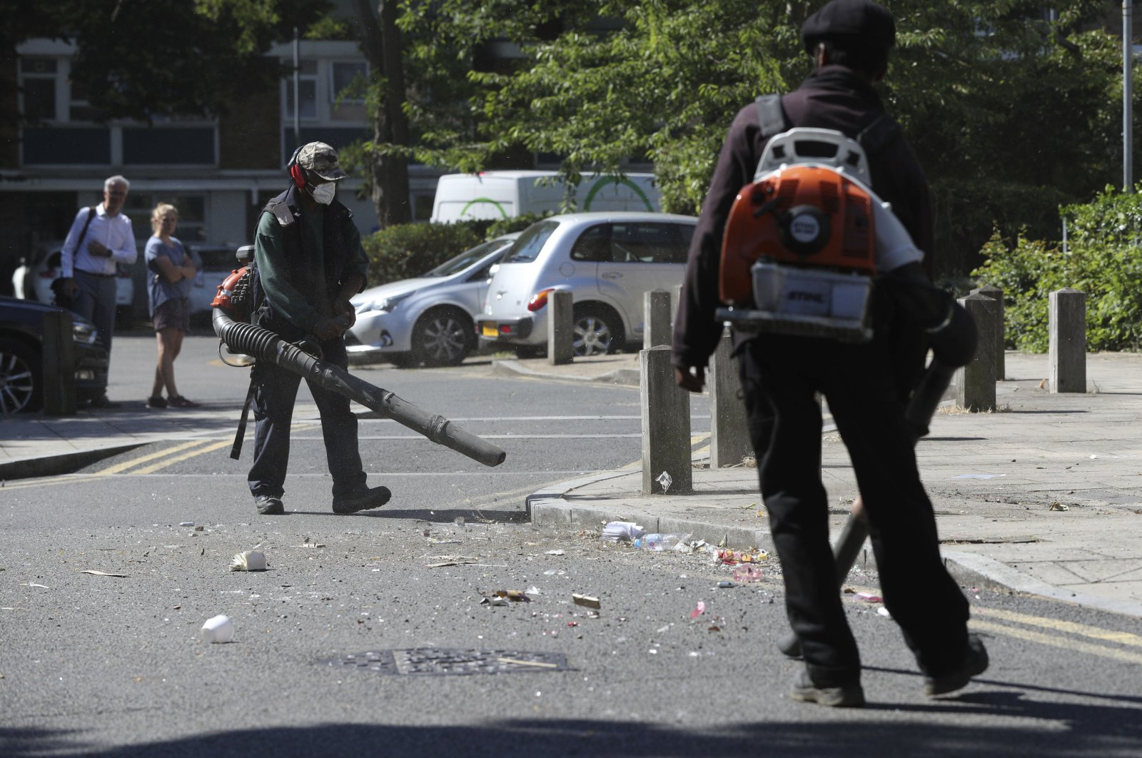 Volunteers clean up following violent confrontations with police that took place overnight in the Brixton area of London, June 25, 2020. (AP Photo)