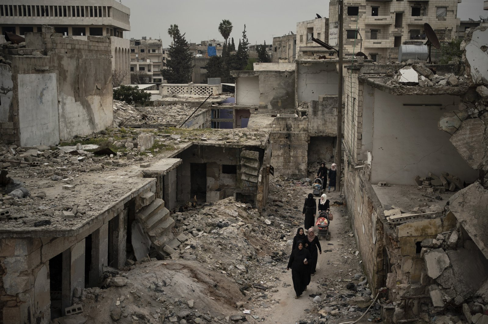 Women walk in a neighborhood heavily damaged by airstrikes in Idlib, March 12, 2020. (AP)