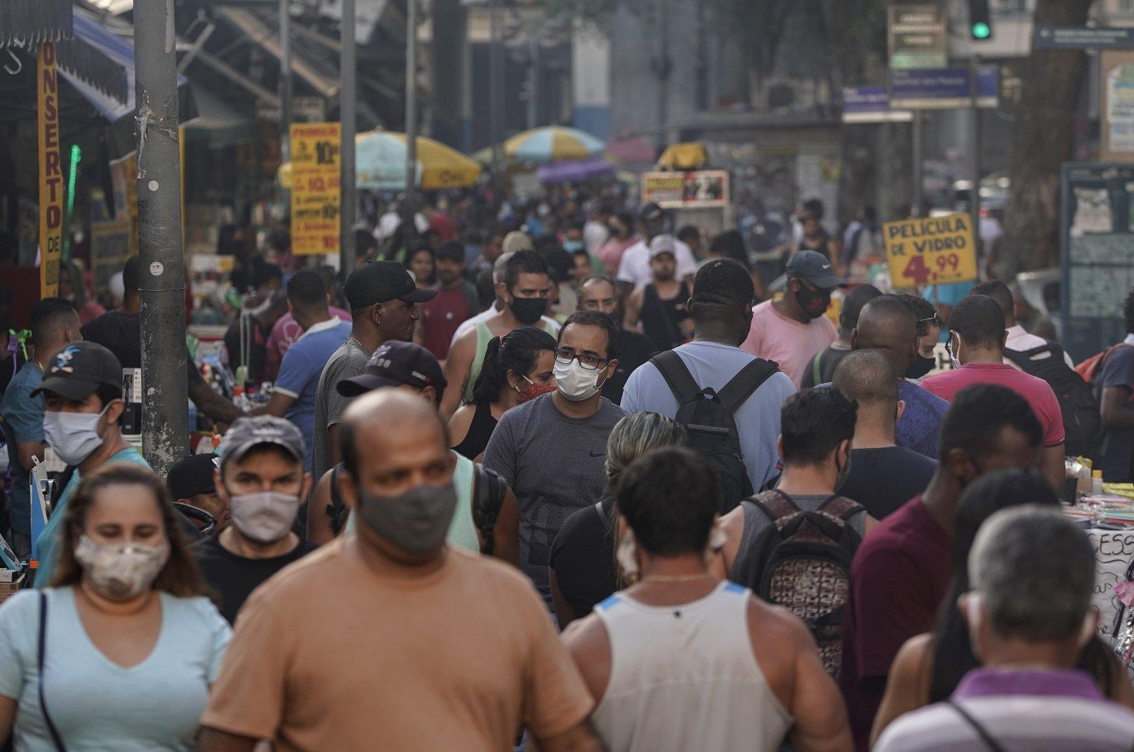 Pedestrians, some wearing protective face masks, walk through a street market in downtown, Rio de Janeiro, Brazil, June 25, 2020. (AP Photo)