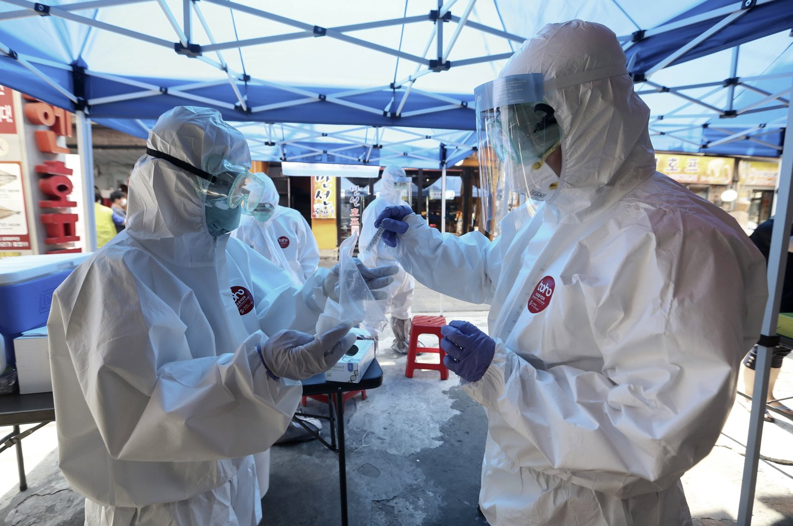 A health official wearing protective gear puts a sample from a person into a plastic bag during COVID-19 testing at a makeshift clinic in Seoul, South Korea, June 5, 2020. (AP Photo)