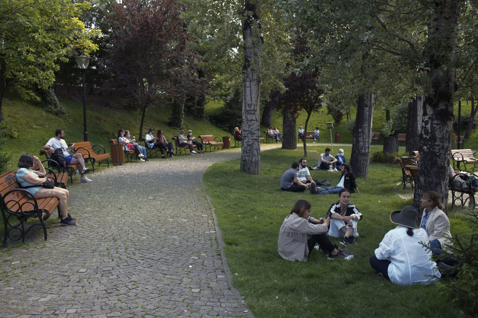 Maskless people sit in a public garden, despite a mandatory rule requiring face masks to be worn, in Ankara, Turkey, June 24, 2020. (AP Photo)
