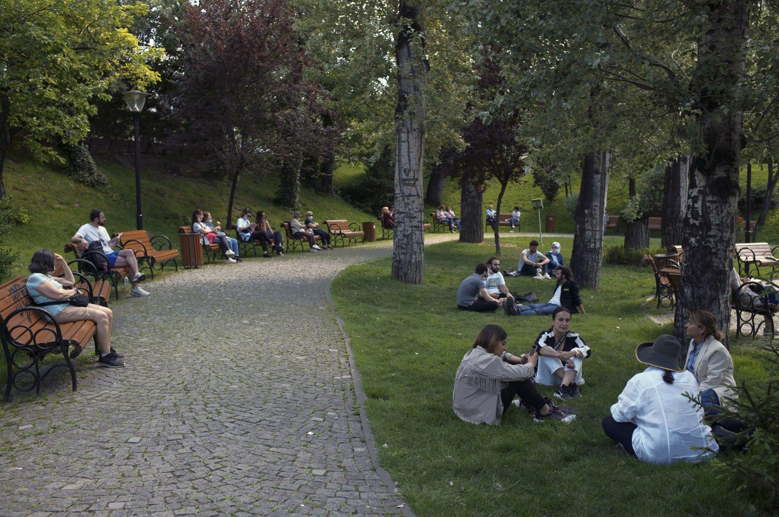 Maskless people sit in a public garden, despite a mandatory rule requiring face masks to be worn, in Ankara, Turkey, June 24, 2020. (AP Photo)