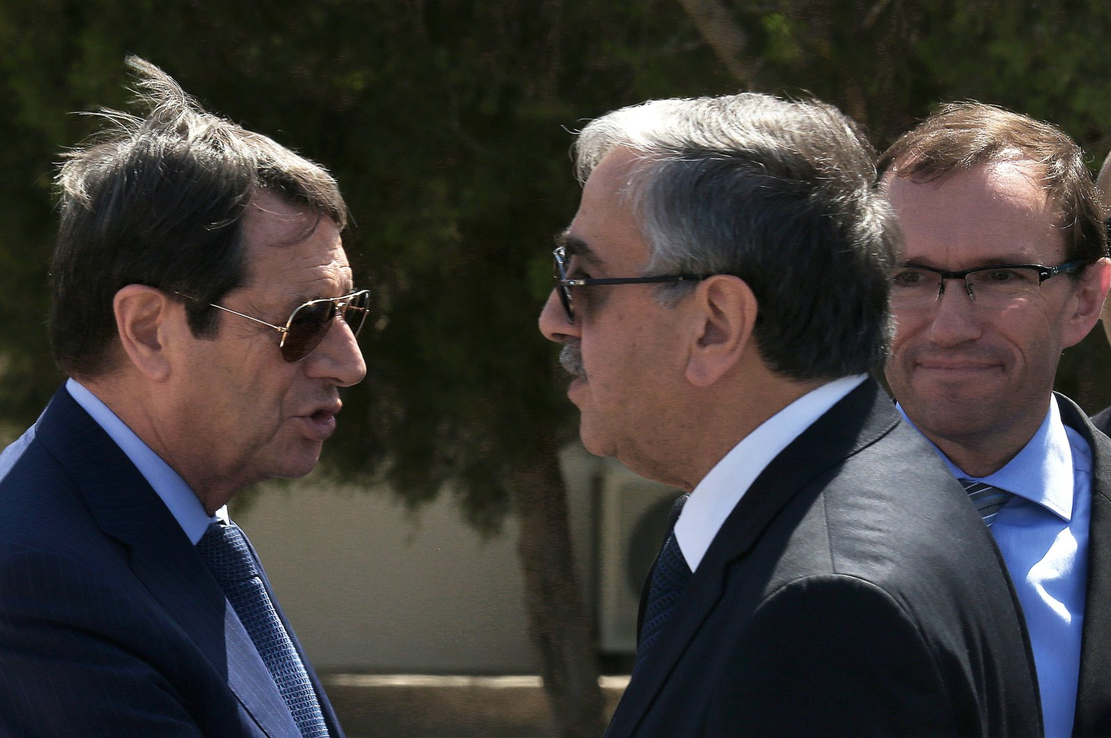 Greek Cypriot leader Nicos Anastasiades (L) and Turkish Republic of Northern Cyprus (TRNC) President Mustafa Akıncı (C) talk as U.N. Special Advisor of the Secretary-General Espen Barth Eide looks on as they leave talks aimed at reunifying the ethnically divided island, Sept. 14, 2016. (AP photo)