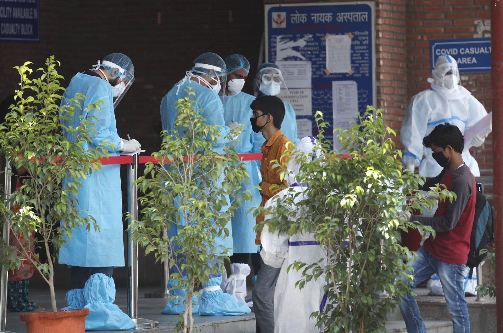 Doctors in personal protective suits check the papers of people whose relatives are admitted in a COVID-19 government designated hospital, in New Delhi, India Tuesday, June 23, 2020. (AP Photo)