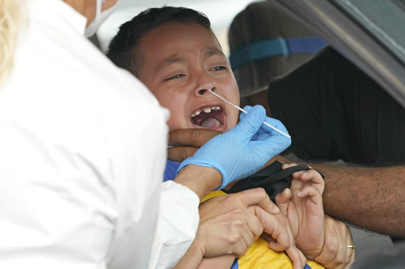 A health care professional takes a sample from Daniel Palacios, 7, at a United Memorial Medical Center COVID-19 testing site in Houston, Texas on June 26, 2020. (AP Photo)