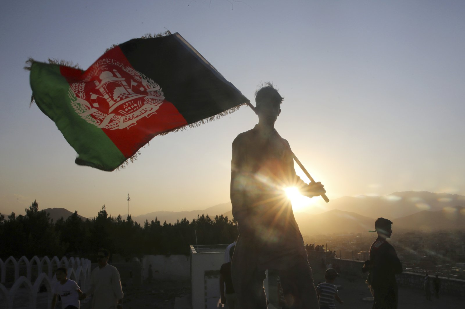 In this Aug. 19, 2019, file photo, a man waves an Afghan national flag during Independence Day celebrations in Kabul, Afghanistan. (AP Photo)