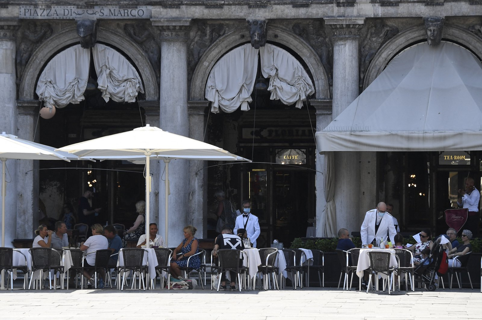 The first umbrellas were mounted that will cover the spaces in front of the premises, enlarged to facilitate the safe arrangement of the tables according to the safety rules on coronavirus, at San Marco square in Venice, Italy, on June 27, 2020. (Reuters Photo)