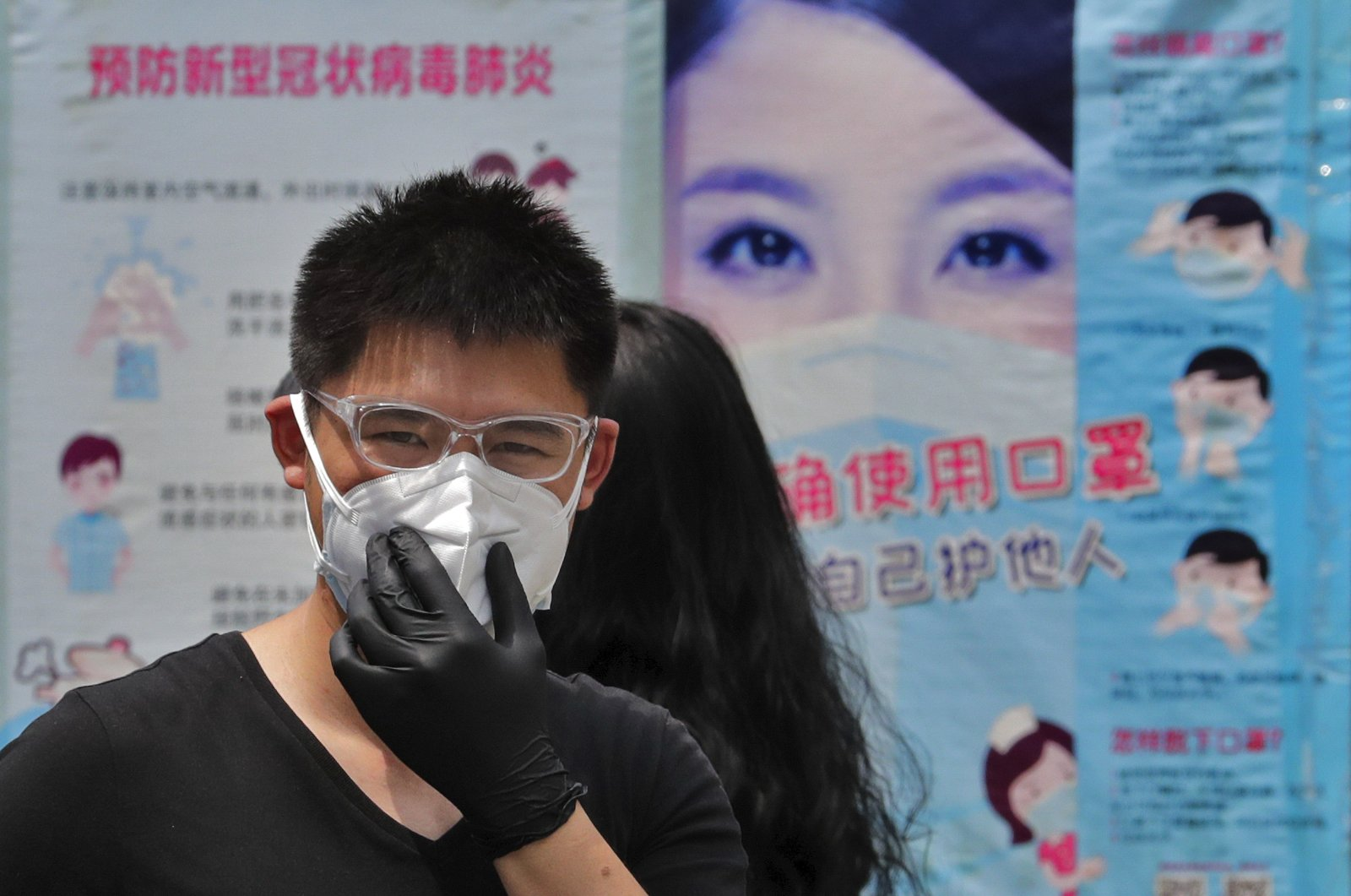 A man wearing gloves adjusts his protective face mask as he walks by posters showing a proper way to wear a face mask in Beijing, June 28, 2020. (AP Photo)