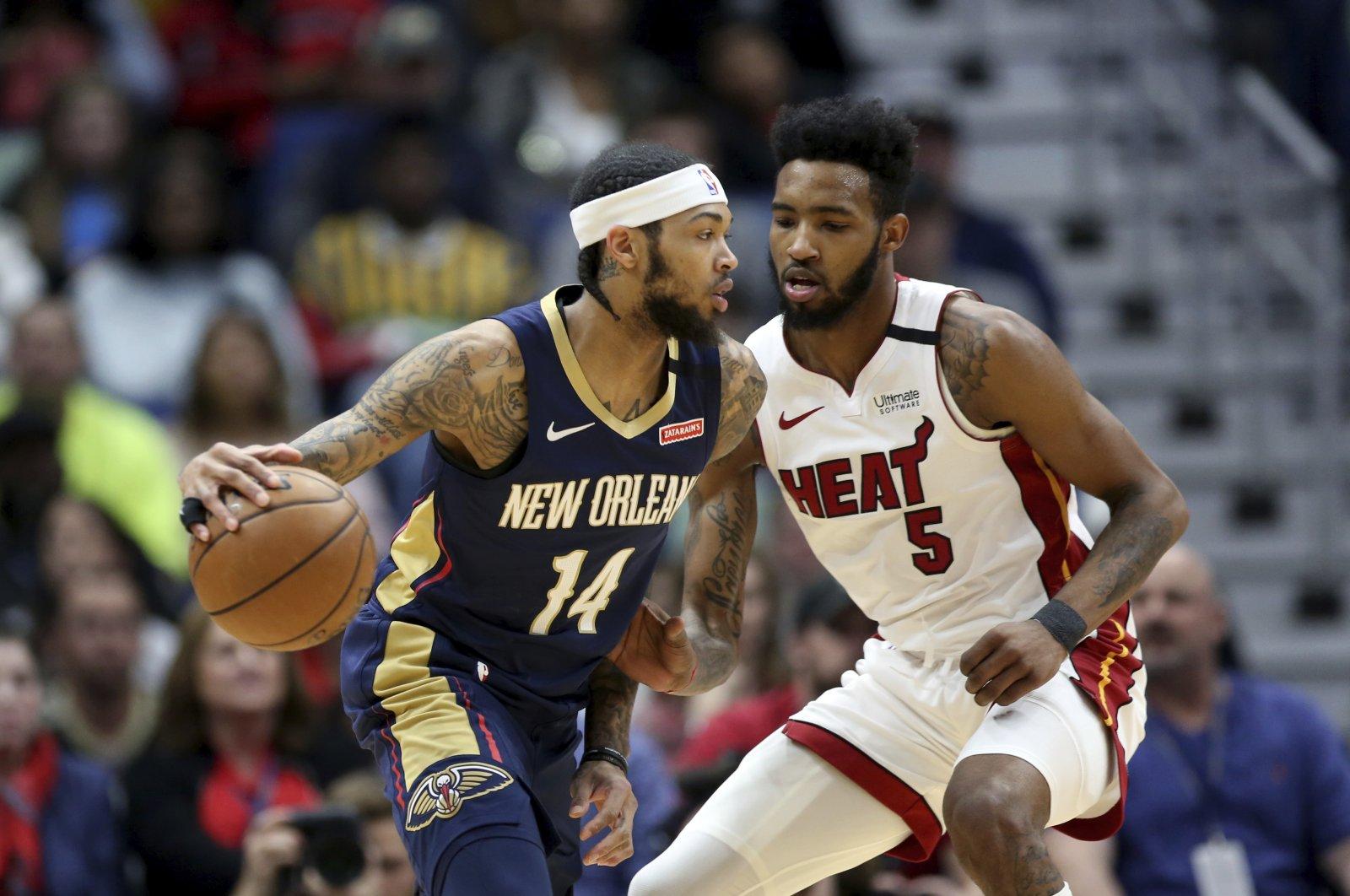 New Orleans Pelicans forward Brandon Ingram (14) dribbles as Miami Heat forward Derrick Jones Jr. (5) defends during an NBA game in New Orleans, U.S., March 6, 2020. (AP Photo)
