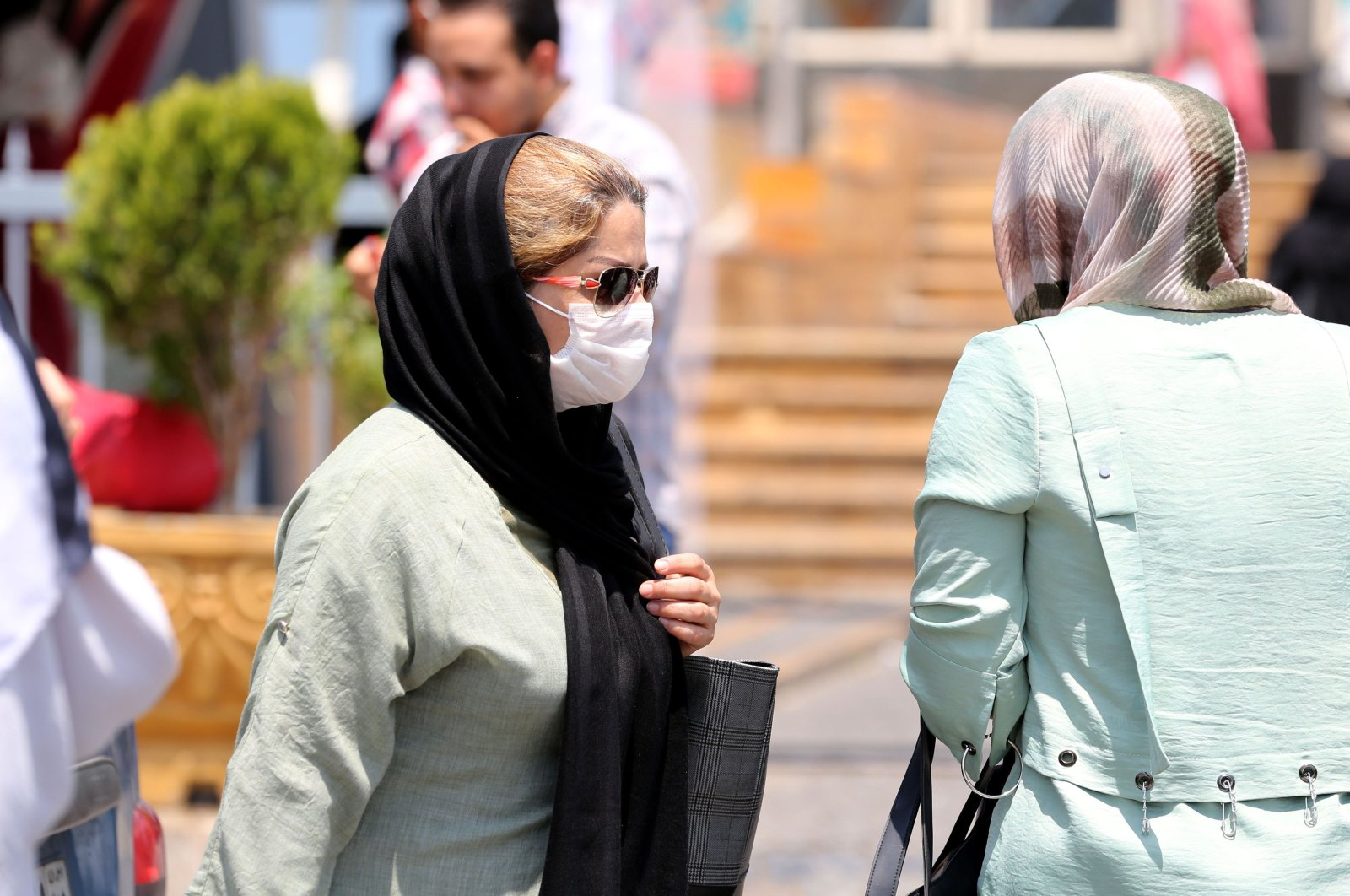 A pedestrian wearing a protective mask due to the coronavirus pandemic, walks along a street in the Iranian capital Tehran, June 28, 2020. (AFP Photo)