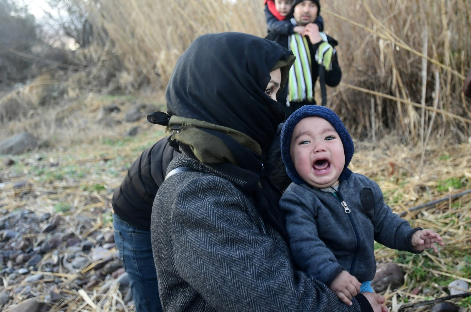 A baby cries as migrants arrive at the village of Skala Sikaminias, on the Greek island of Lesbos, after crossing on a dinghy the Aegean sea from Turkey, March 2, 2020. (AP Photo)