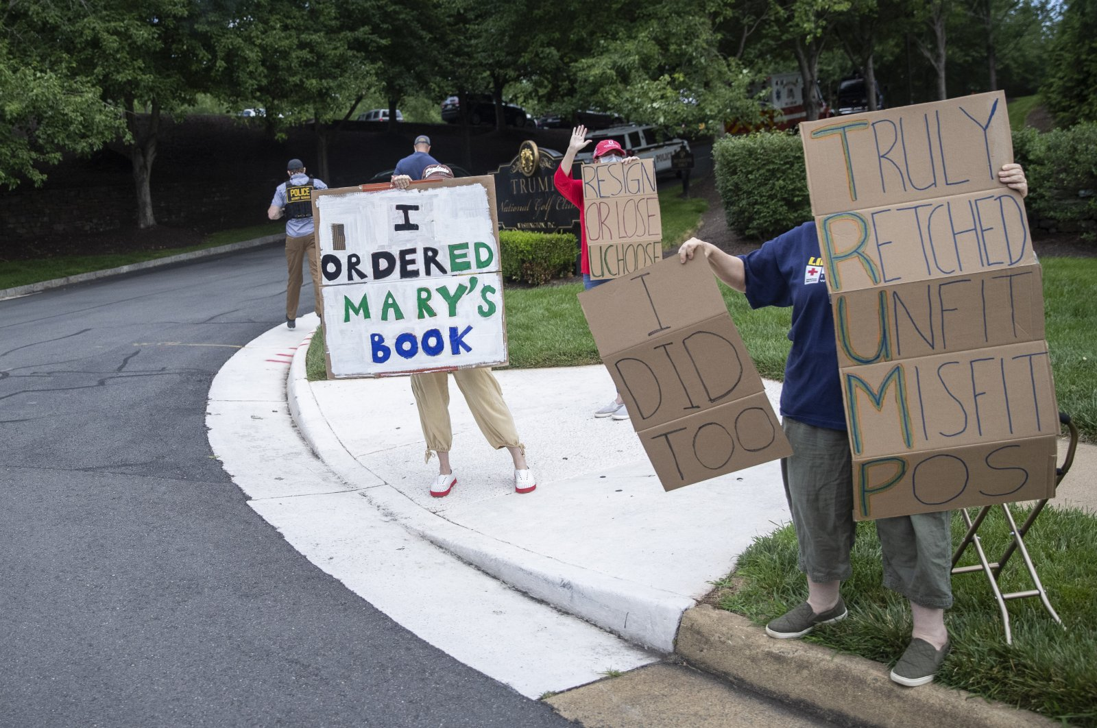 Protesters hold signs as President Donald Trump arrives at Trump National Golf Club, Sunday, June 28, 2020, in Sterling, Va. (AP Photo)