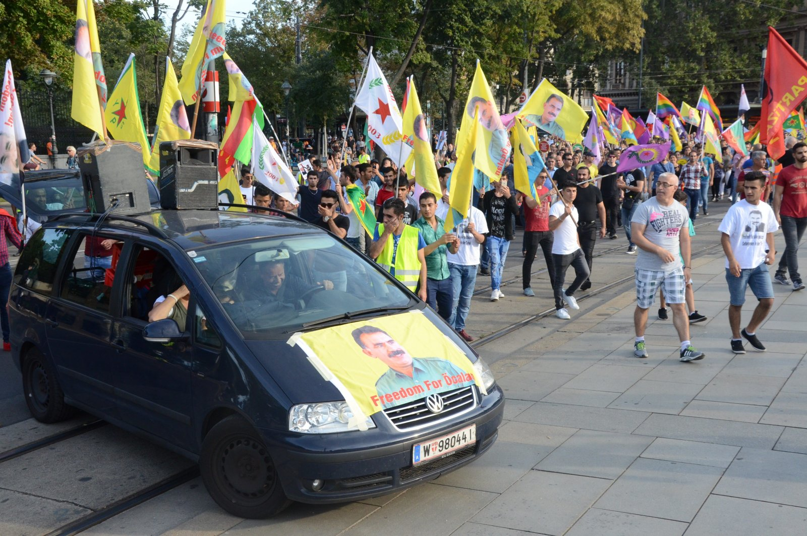 Pro-PKK protesters wave flags of the terrorist organization and a picture of imprisoned terrorist leader Abdullah Öcalan is seen on a vehicle in the Austrian capital Vienna, June 28, 2020. (AA Photo)