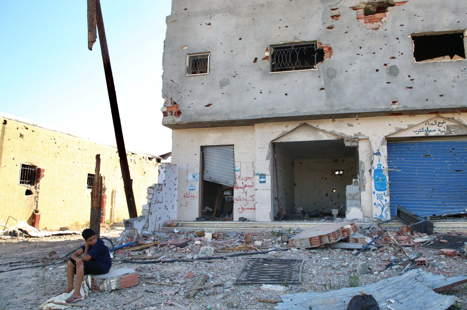A boy sits in front of a destroyed building in the Libyan capital Tripoli, June 27, 2020. (AA Photo)