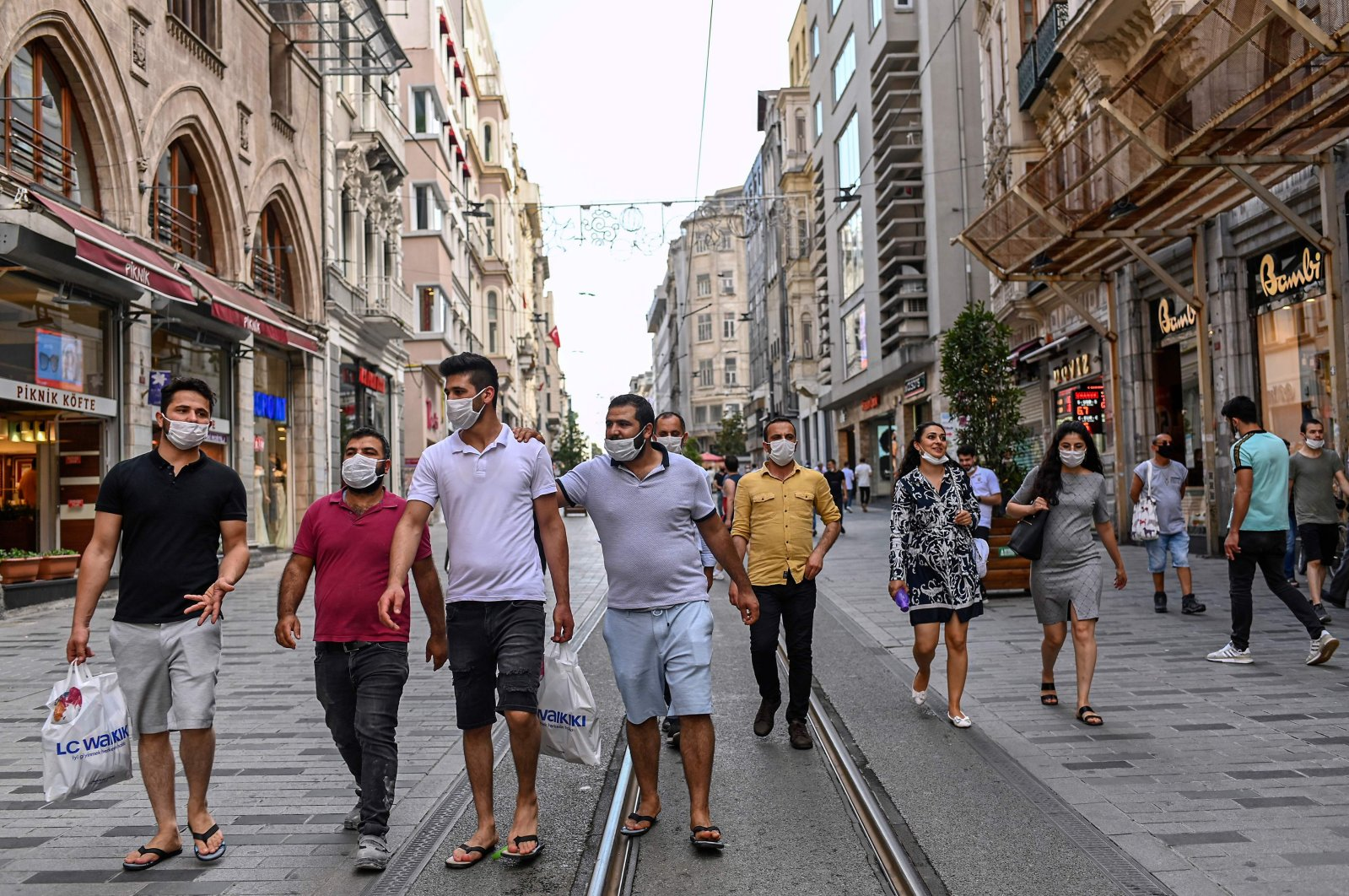 People wearing protective face masks to curb the spread of the coronavirus walk along the popular shopping hub, Istiklal Avenue, Istanbul, Turkey, June 25, 2020. (AFP Photo)