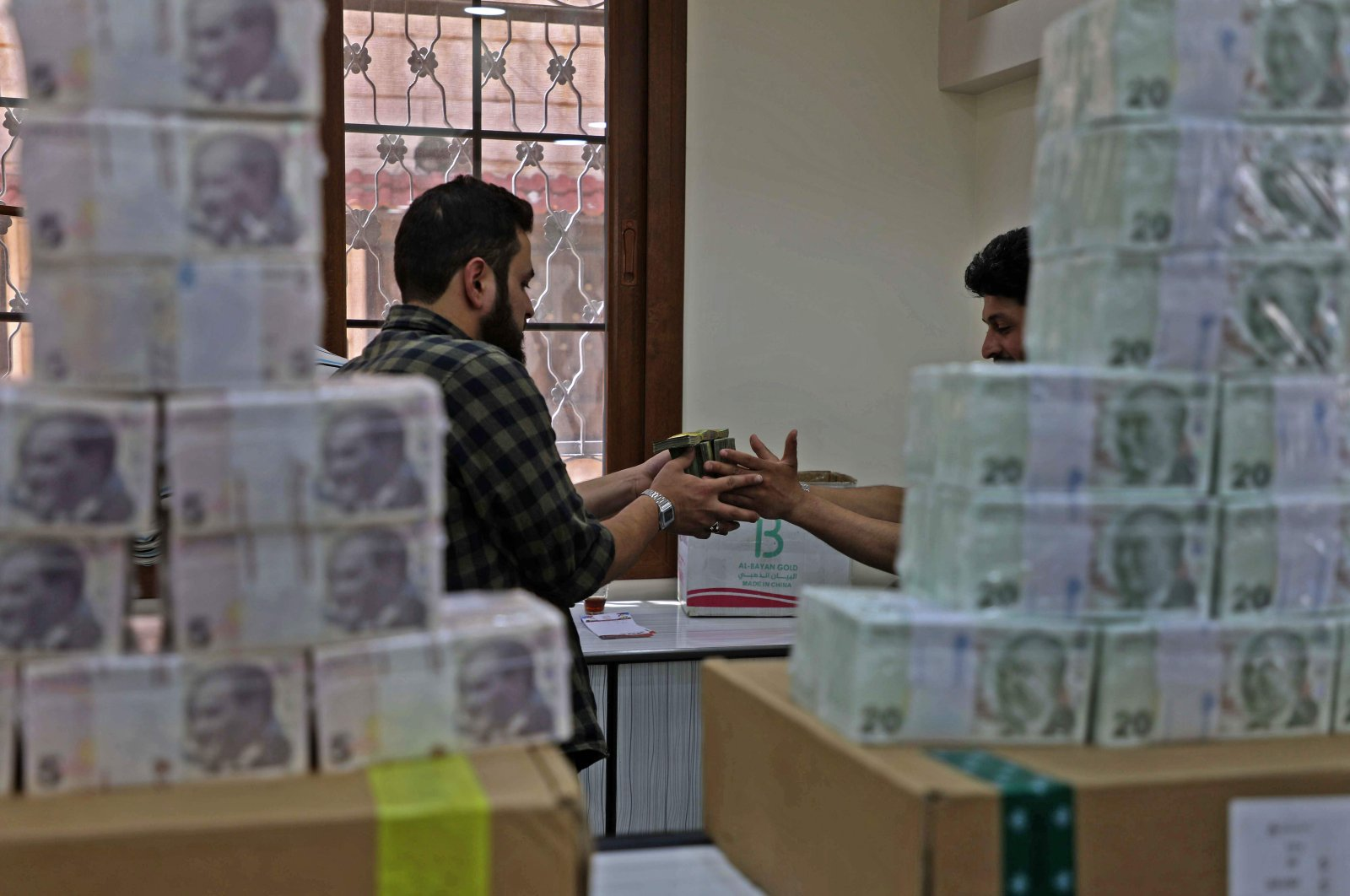 Employees sort Turkish lira banknotes at a bank in the town of Sarmada in Syria's northwestern Idlib province, June 14, 2020. (AFP Photo)