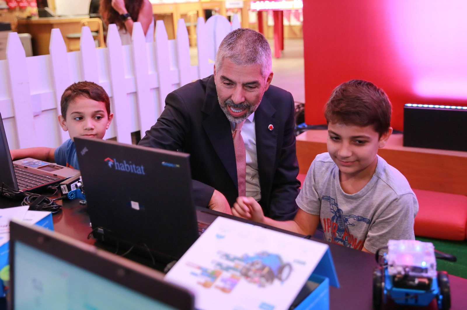 The chairman of Turkey Vodafone Foundation Hasan Süel sits between two children receiving coding courses. (Takvim File Photo)