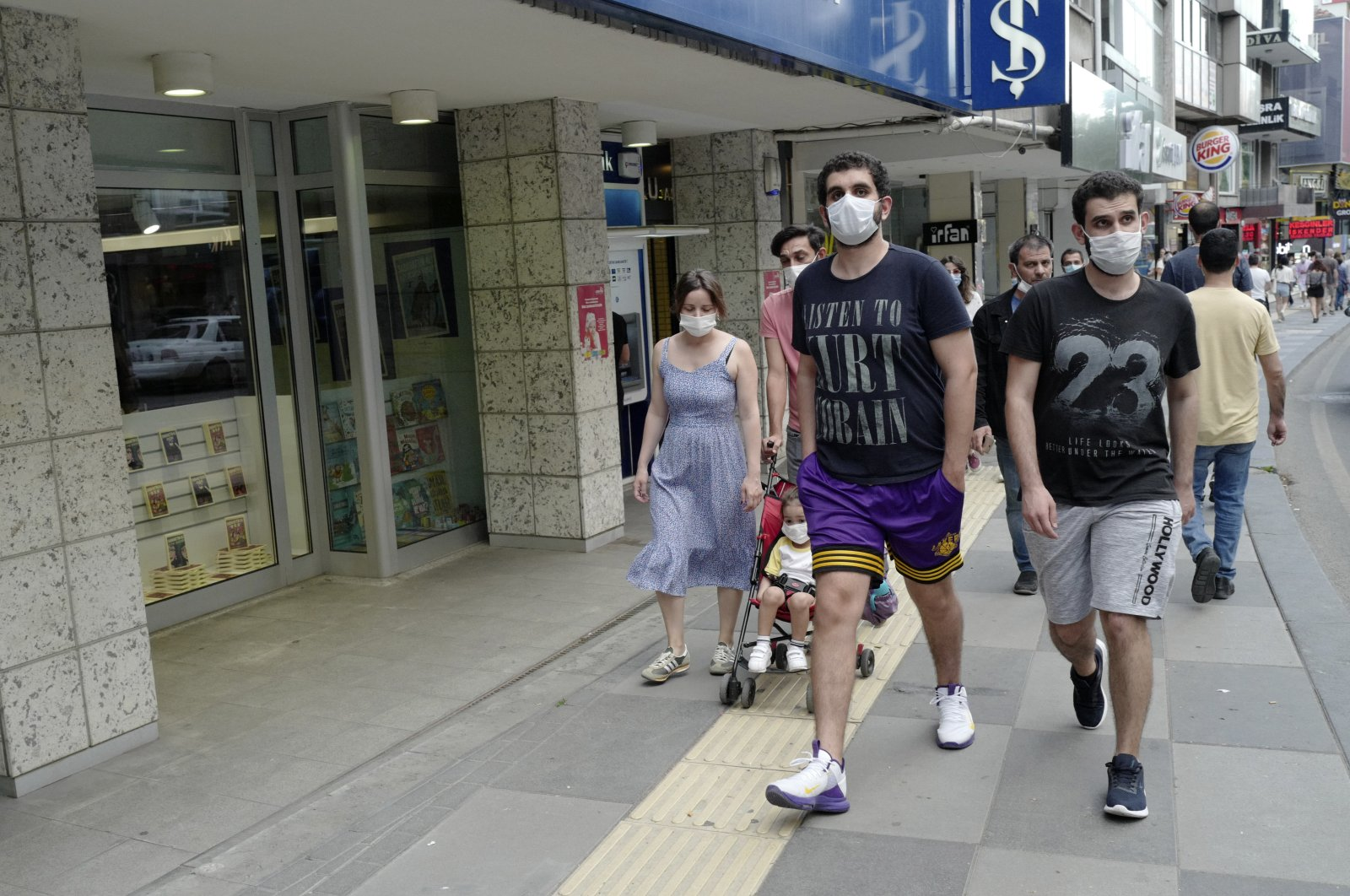 People wearing face masks to protect against the spread of coronavirus, walk in a popular shopping street after a nine-hour curfew, in Ankara, Turkey, June 28, 2020.