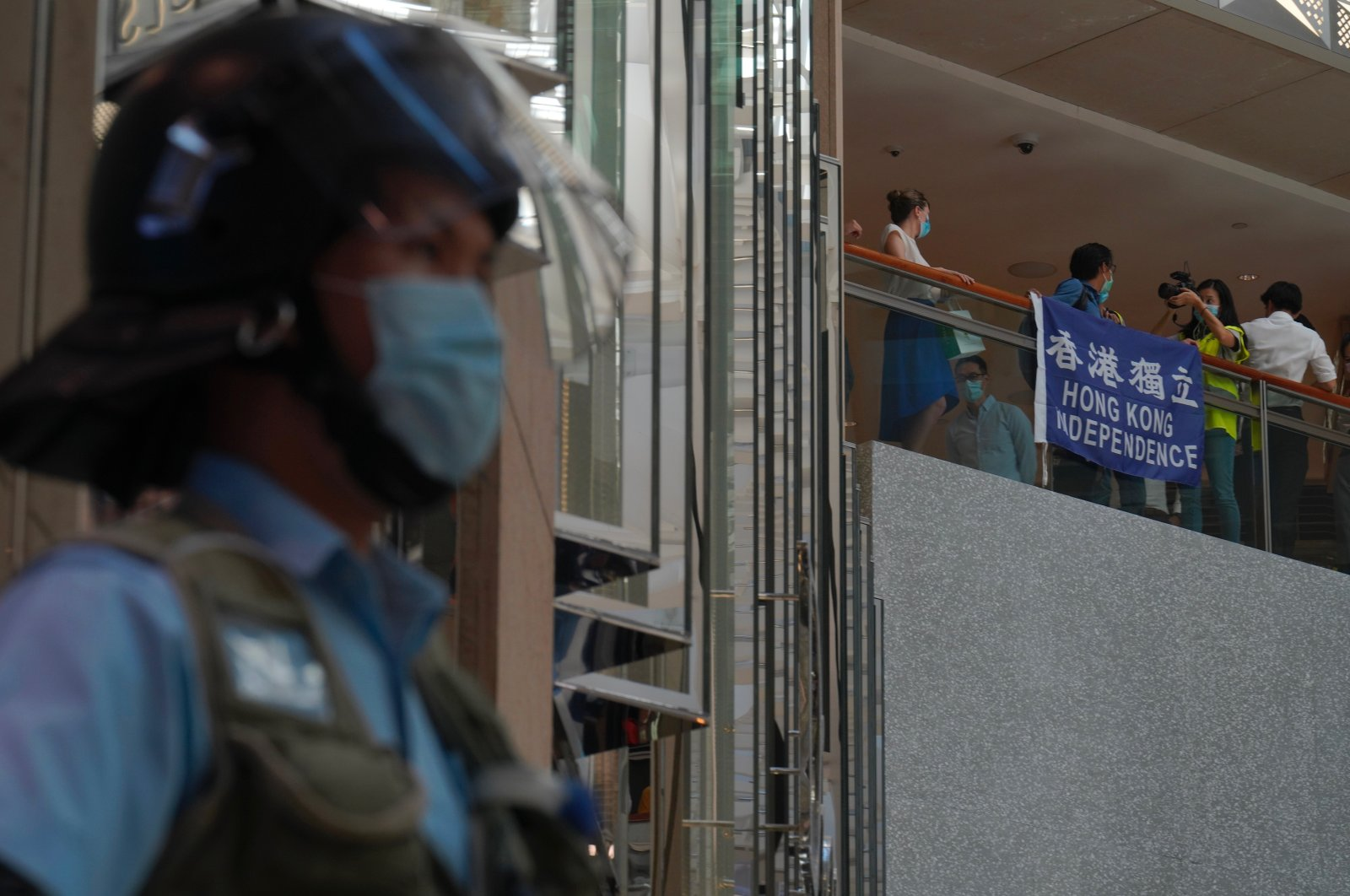 A police officer stands guard as protesters gather at a shopping mall in Central during a pro-democracy protest against Beijing's national security law in Hong Kong, June 30, 2020. (AP Photo)