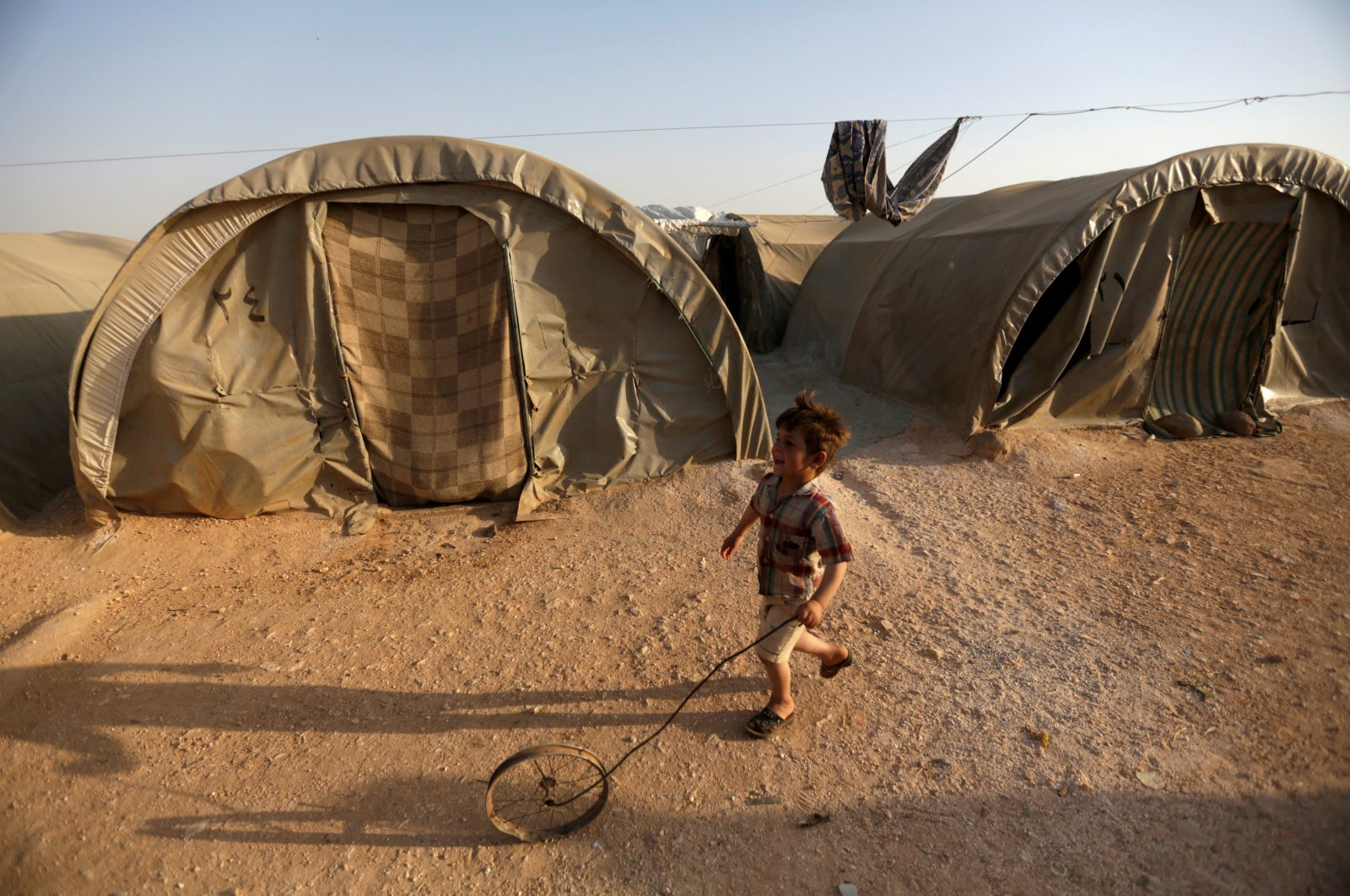 An internally displaced Syrian boy plays with a wheel in Jrzinaz Camp in the southern part of Idlib, Syria, June 21, 2016. (Reuters Photo)