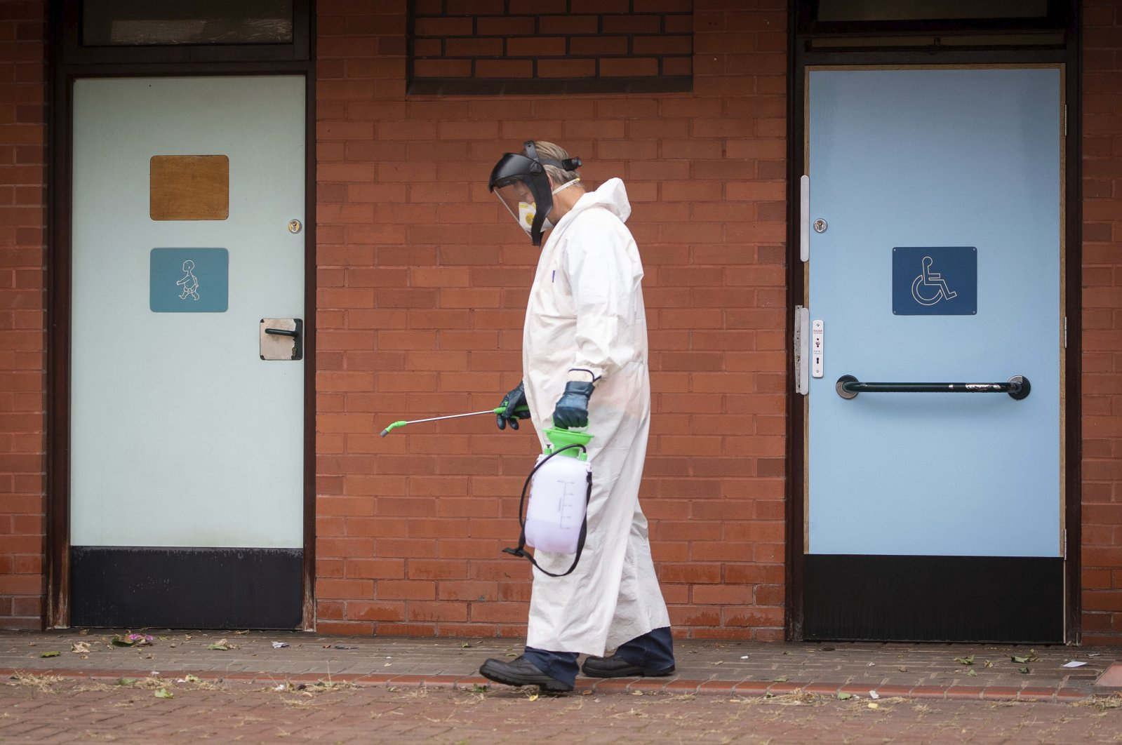 A worker for Leicester City Council disinfects public toilets, Leicester, June 29, 2020. (AP Photo)