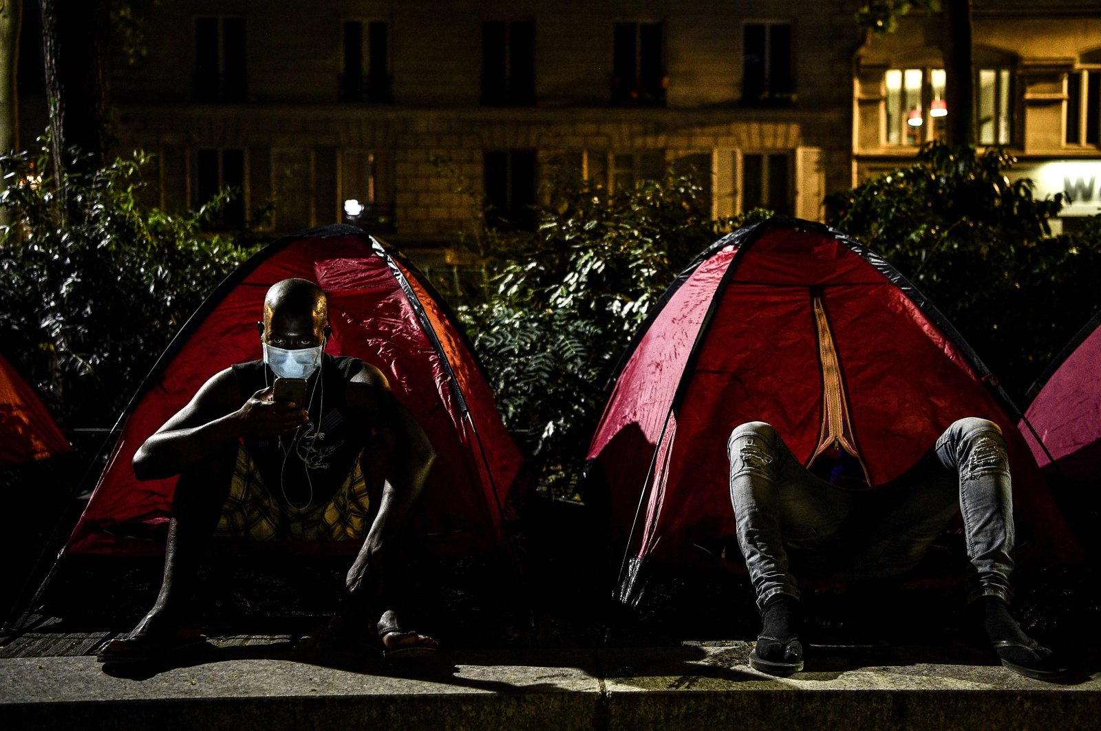 A young migrant checks his phone outside a tent at a makeshift camp set up by volunteers of charities Medecins Sans Frontieres (MSF – Doctors Without Borders) and Utopia 56 at a public park in Paris early on June 30, 2020. (AFP Photo)