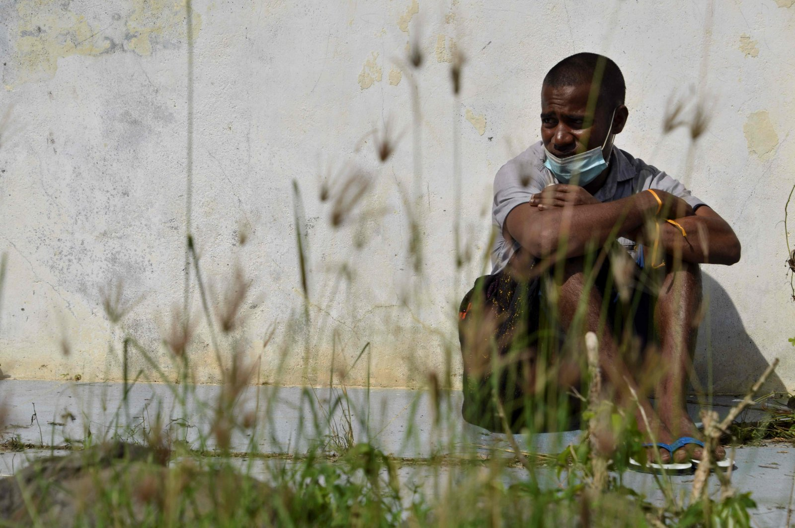A Rohingya from Myanmar sits outside an immigration detention center in Lhokseumawe, in Indonesia's North Aceh Regency, June 26, 2020. (AFP Photo)