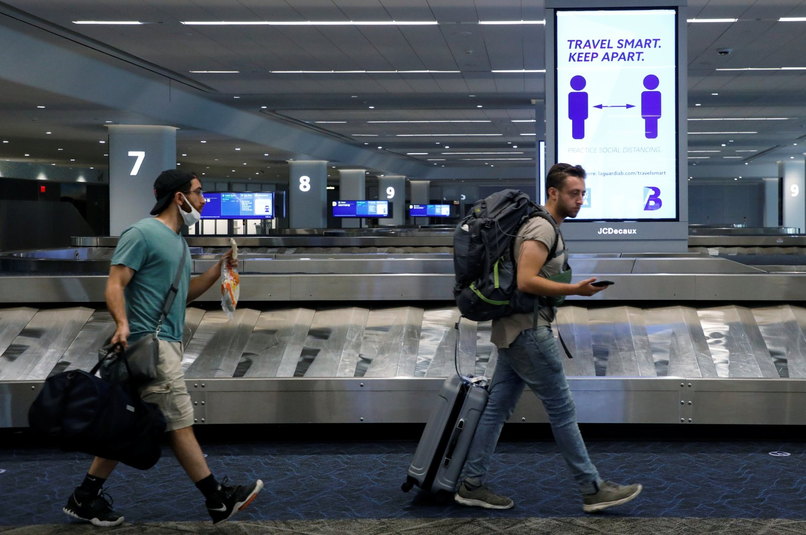 Travelers pass a sign alerting them to distance at LaGuardia Airport, during the outbreak of the coronavirus disease (COVID-19), in New York, U.S., June 29, 2020. (Reuters Photo)