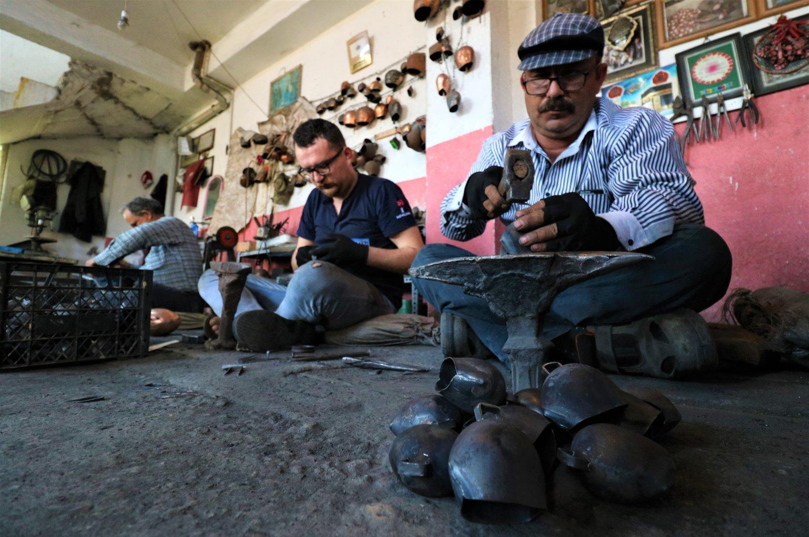 The Çancı family crafts bells in their workshop, in Manisa, Turkey, June 30, 2020. (IHA Photo)
