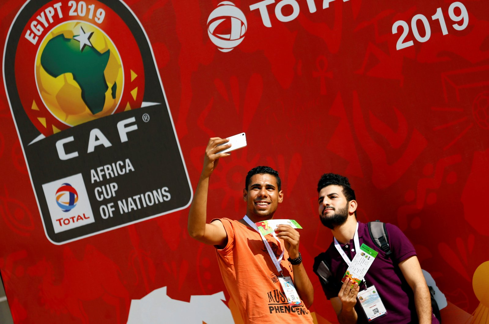 Youths take a selfie with opening soccer match tickets for African Nation Cup between Egypt and Zimbabwe in front of the tournament banner, Cairo, Egypt, June 12, 2019. (Reuters Photo)