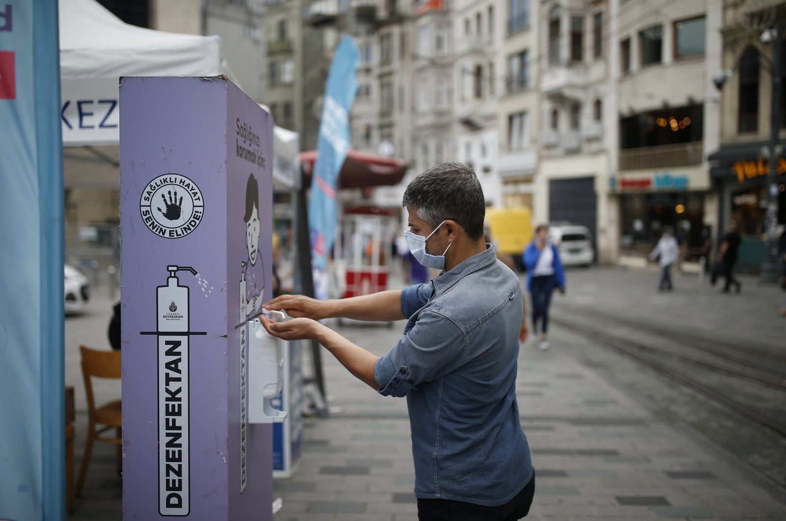 A man, wearing a protective mask against the spread of coronavirus, uses disinfectant from a public station on Istiklal street, the main shopping street in Istanbul, Thursday, June 18, 2020. (AP Photo)