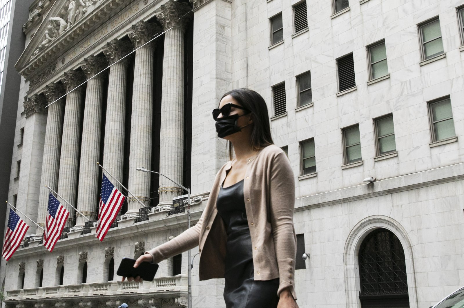 A woman wearing a mask passes the New York Stock Exchange, Tuesday, June 30, 2020, during the coronavirus pandemic. (AP Photo)