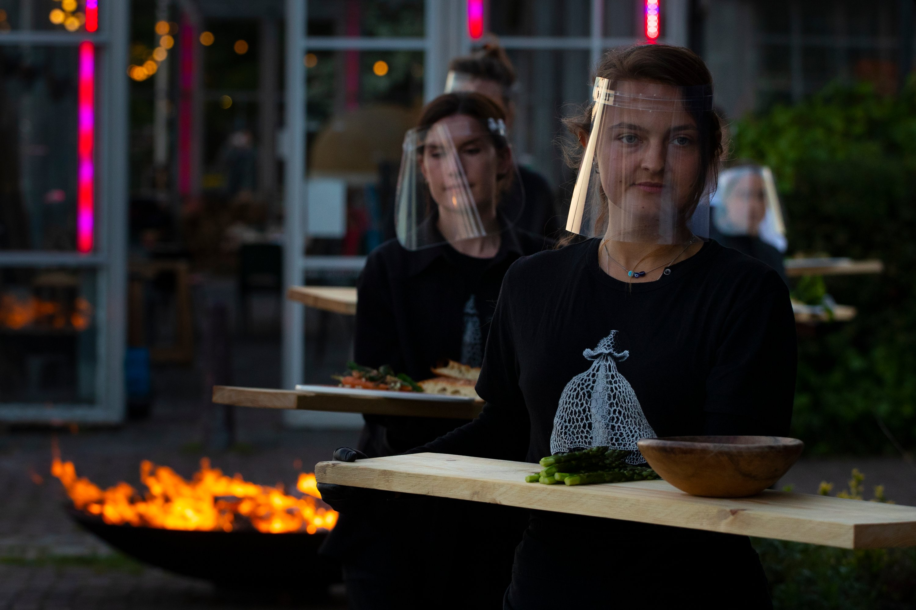 Staff at the Mediamatic restaurant serve food to volunteers seated in small glasshouses during a try-out of a setup which respects social distancing abiding by government directives to combat the spread of the COVID-19 coronavirus in Amsterdam, Netherlands, Tuesday, May 5, 2020. (AP Photo)