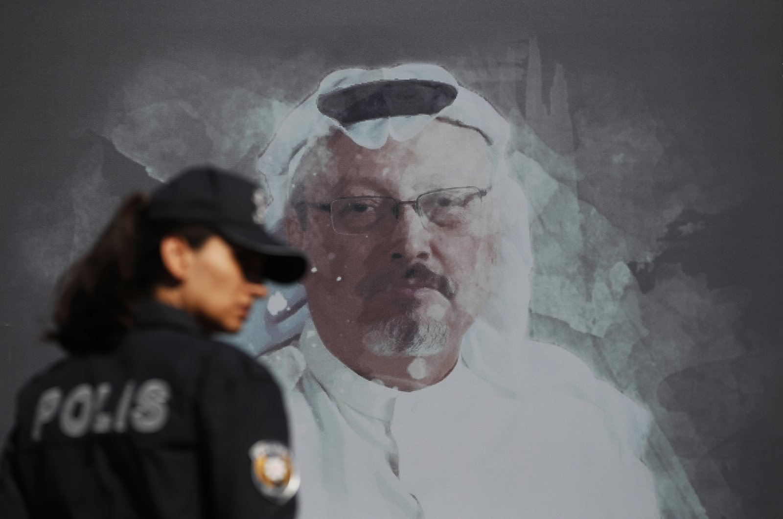 A Turkish police officer walks past a picture of slain Saudi journalist Jamal Khashoggi prior to a ceremony, near the Saudi Arabia consulate in Istanbul, marking the one-year anniversary of his death, Wednesday, Oct. 2, 2019. (AP Photo)