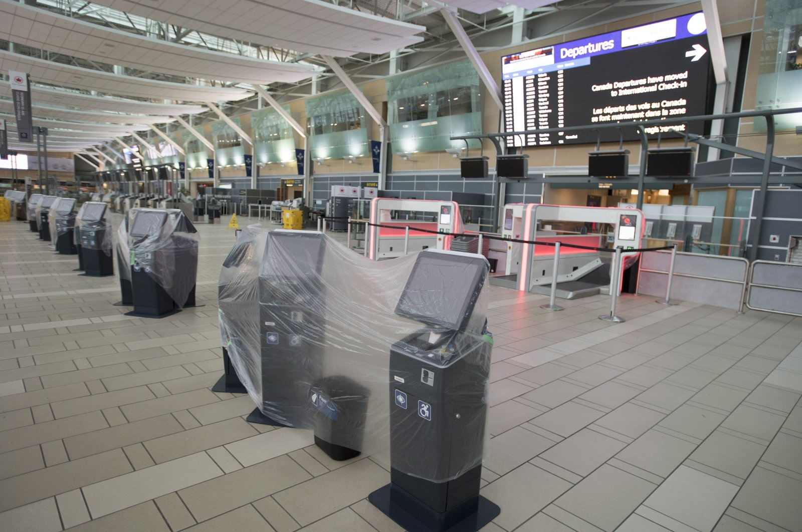Check-in kiosks are covered in plastic at the domestic check-in, at Vancouver International Airport, Vancouver, Canada, June 9, 2020. (AP Photo)